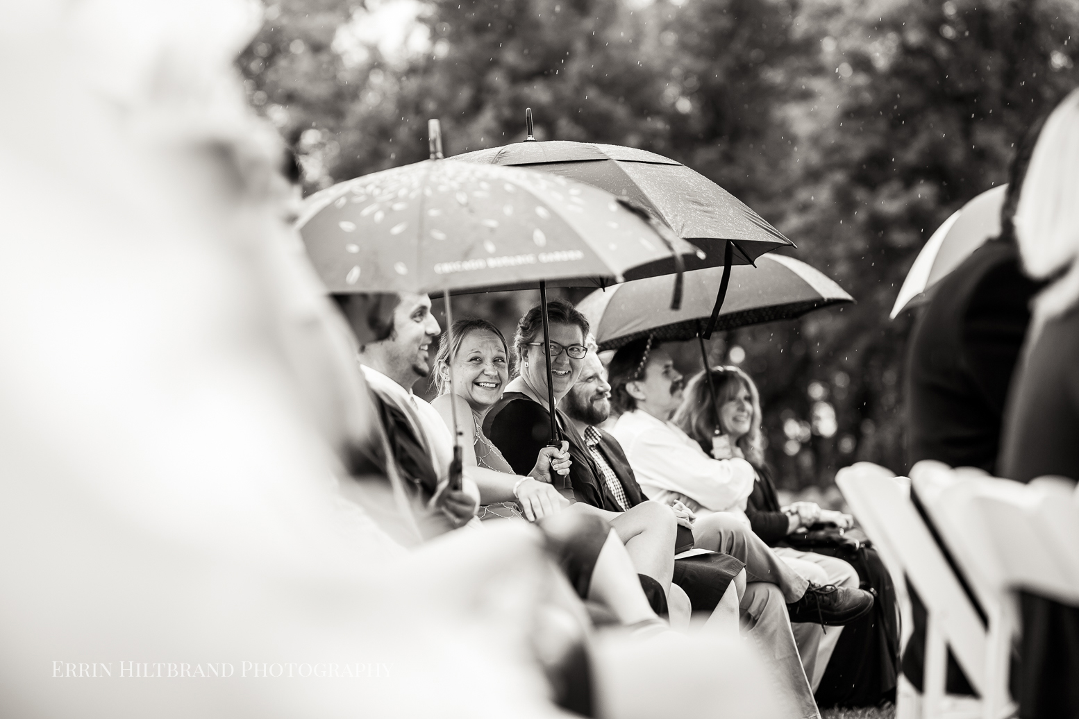 Wedding guests seated during the ceremony, holding umbrellas