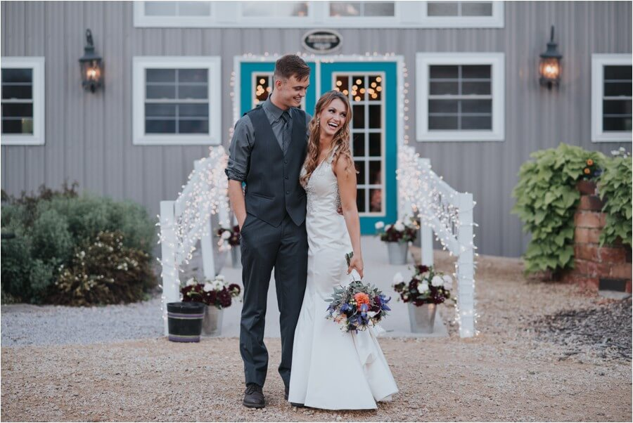 Bride and groom standing in front of the barn