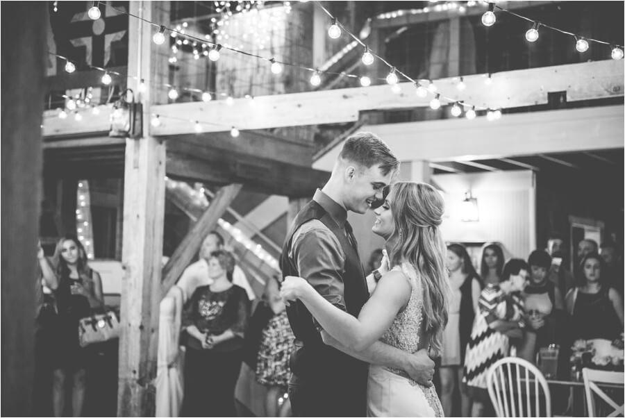 Bride and groom dancing inside the barn under lights