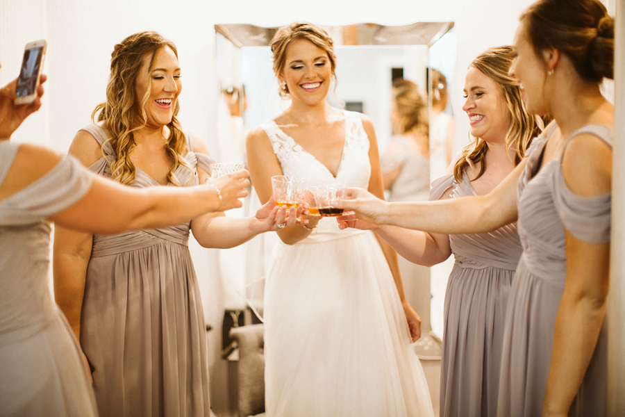 Bride and bridesmaids toasting with beverages while getting ready