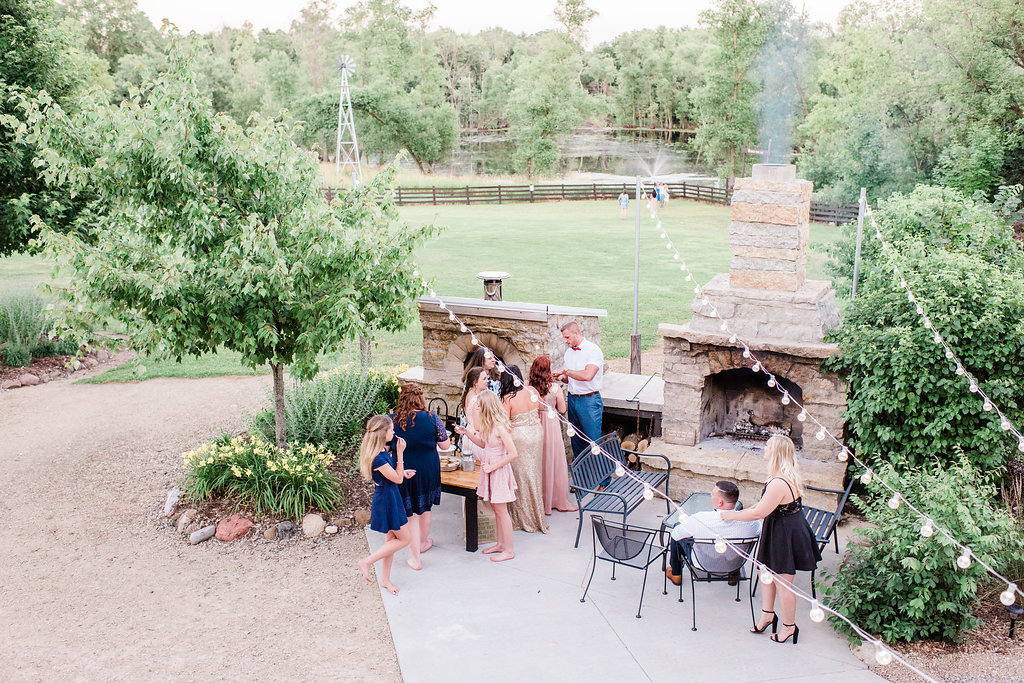 Wedding guests by the fireplace outside