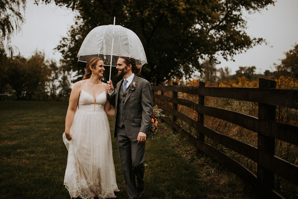Bride and groom holding an umbrella outside by a fence