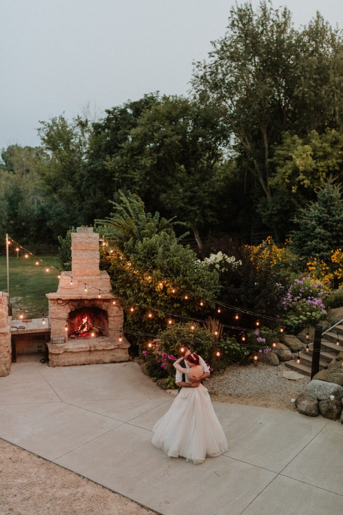 Bride and groom dancing by an outdoor fireplace under lights