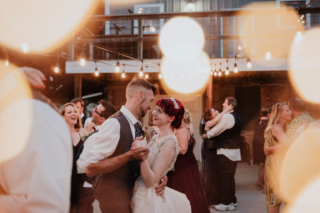 Bride and groom dancing outside under the lights