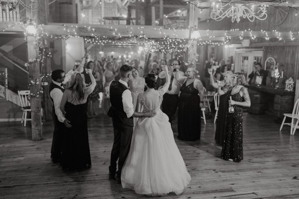 Bride and groom dancing inside the barn under lights