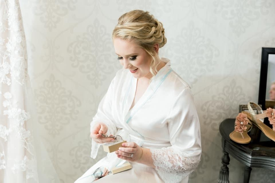 Bride looking at wedding jewelry while getting ready