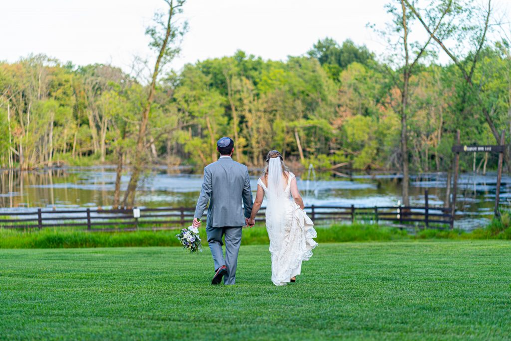 Bride and groom holding hands and walking towards the pond