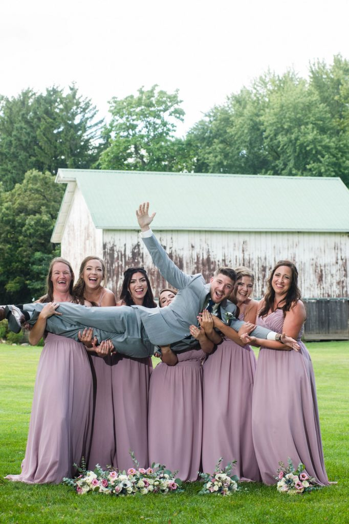 Bridesmaids and groom in front of a barn