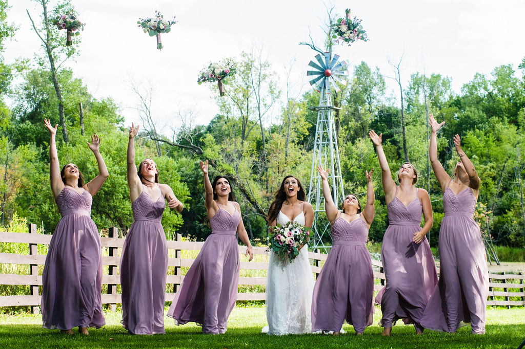 Bride and bridesmaids throwing flowers in the air outside by a fence